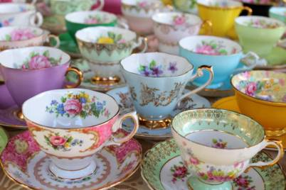 Vintage pastel and floral china tea cups lined up in rows and in stacks.